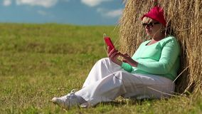 Woman sits on a green grass near haystack and uses cell phone stock video footage