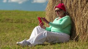 Woman sits on a green grass near haystack and uses cell phone stock video