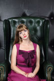 Woman in sits in green leather armchair in room Stock Image