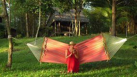 The woman sits in a hammock with the smartphone. The woman in a straw shlyama and in a red dress sits on a hammock in stock footage