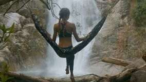 Woman Sits on Hammock Suspended on Tree Branches. Backside view woman sits on hammock suspended on tree branches and takes pleasure in waterfall view among sharp stock video footage