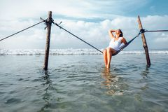 Woman sits in hammock swing over ocean surf line - island summer Royalty Free Stock Photos