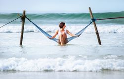 Woman sits in hammock swing over ocean surf line - island summer Royalty Free Stock Photography