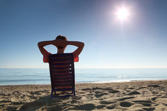Woman sits heaving up hands for head by person. Woman sits on  plastic chair heaving up hands for  head by  person to  sea Stock Image