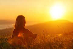 Woman sits with her back in the field and admires the sunset in mountains Royalty Free Stock Photos