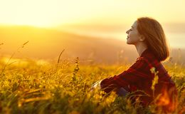 Woman sits with her back in the field and look sunset in the mou Royalty Free Stock Photo