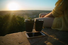 Woman sits on the hill with cups of cofee Royalty Free Stock Image