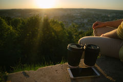 Woman sits on the hill with cups of cofee Stock Photo