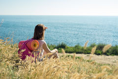 Woman sits on a hillside and looks out to sea Stock Images