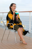 Woman sits and holds cocktail in glass. Beautiful woman wrapped in blanket sits on chair on cruise liner deck and holds cocktail in glass Royalty Free Stock Photography