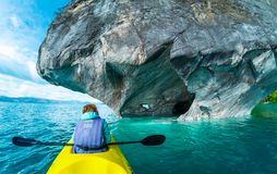 Woman sits in kayak. And explores the Marble Caves and rocks on the lake of General Carrera, Chile Stock Photography