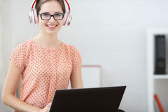 Woman sits with a laptop on his lap, listening to music and learning. Smiling and looking into the camera. Stock Photo