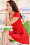Woman sits at little table in cafe Stock Photos