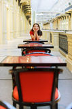 Woman sits at little table in cafe Royalty Free Stock Photography