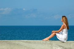 Woman sits and looks at the sea Royalty Free Stock Image