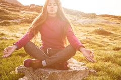 Woman sits in lotus position at sunrise Royalty Free Stock Images