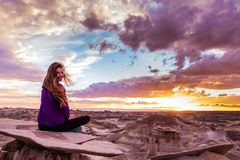 Woman Sits on Mountain Under Cloudy Sky at Sunset Royalty Free Stock Photo