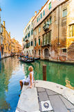 Woman Sits Near A Canal And Gondolas Admires In Venice Stock Photos