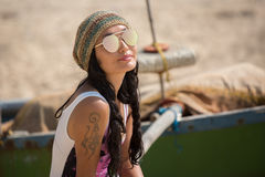 A woman sits near a boat wearing sunglasses and a hat. On the beach Royalty Free Stock Photo