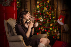 Woman sits near christmas tree Royalty Free Stock Image