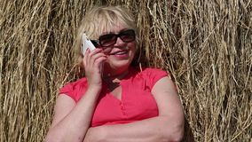 Woman sits near haystack and communicates via mobile phone stock video