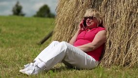 Woman sits near haystack and communicates via mobile phone stock video footage