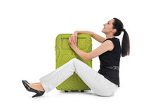 Woman sits near suitcase. Stock Images