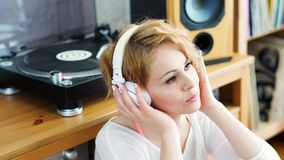 Woman sits next to the turntable and listens to music. Beautiful woman sitting next to a turntable with headphones on her head and listens to music stock video footage