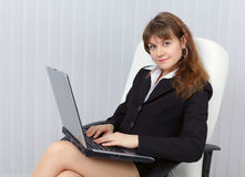 Woman sits in office armchair with laptop Royalty Free Stock Images