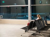 Free Woman Sits On The Black Bench At The Airport Departure Lounge And Looks To The Phone Display Royalty Free Stock Photography - 148606217