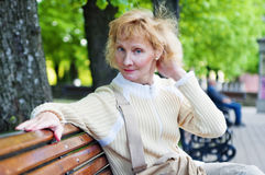 Woman sits on a park bench Royalty Free Stock Photos