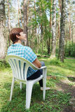 Woman sits in a plastic armchair outdoor Stock Photography