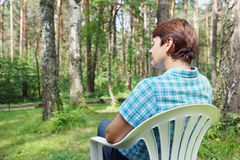 Woman sits in a plastic armchair in the pine forest Stock Photo
