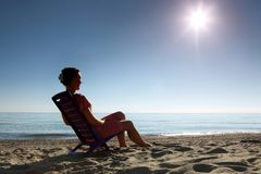 Woman sits on plastic chair sideways on beach. Woman sits on  dark blue plastic chair sideways and becomes tanned in  morning on  beach Royalty Free Stock Photo