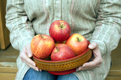 Woman sits on porch and holds bowl with apples close up Stock Image