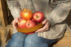 Woman sits on porch and holds bowl with apples close up Stock Photo