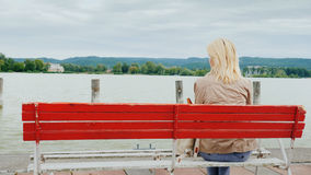 A woman sits on a red bench, admiring the view of the lake. Back view. Rest on Lake Balaton in Hungary Stock Photo