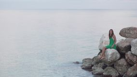 A woman sits on rocks near the sea. stock footage