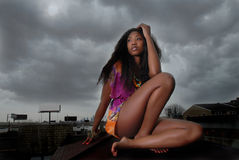 Woman sits on rooftop. African american woman thinking as she stares, as she leans on her arms royalty free stock images