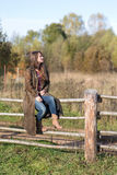 Woman sits on a rural fence Royalty Free Stock Images