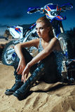 The woman sits on sand near the motorcycle Royalty Free Stock Photography
