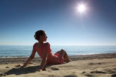 Woman sits on sand near sea. Woman in  morning sits on sand leaning against hands near  sea and becomes tanned Royalty Free Stock Images