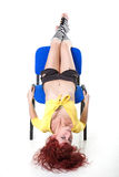 Woman sits on seat heels over head. Sexy young red-haired woman in yellow blouse and black shorts sits on seat heels over head Royalty Free Stock Photos