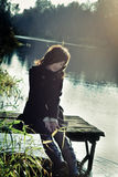 Woman sits on the small wooden bridge. On background river Royalty Free Stock Photography