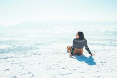 Woman sits on the snowy mountain hill over the city. Sunny winter beautiful weather day stock photography