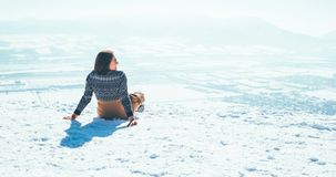 Woman sits on the snowy mountain hill over the city. Sunny winter beautiful weather day stock photo