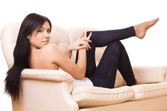 Woman sits on sofa Royalty Free Stock Photo