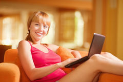 Woman sits on sofa with laptop Stock Photography