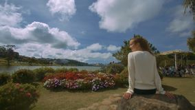 Woman Sits on Stone Enjoys Scenery against River. Closeup backside view blonde girl in white sweater sits on stone and enjoys scenery against cafe near river stock video footage