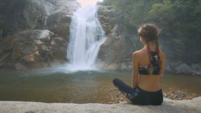 Woman Sits on Stone Takes Pleasure in Waterfall View. Closeup backside view slim woman sits on stone and takes pleasure in wonderful waterfall view running among stock footage